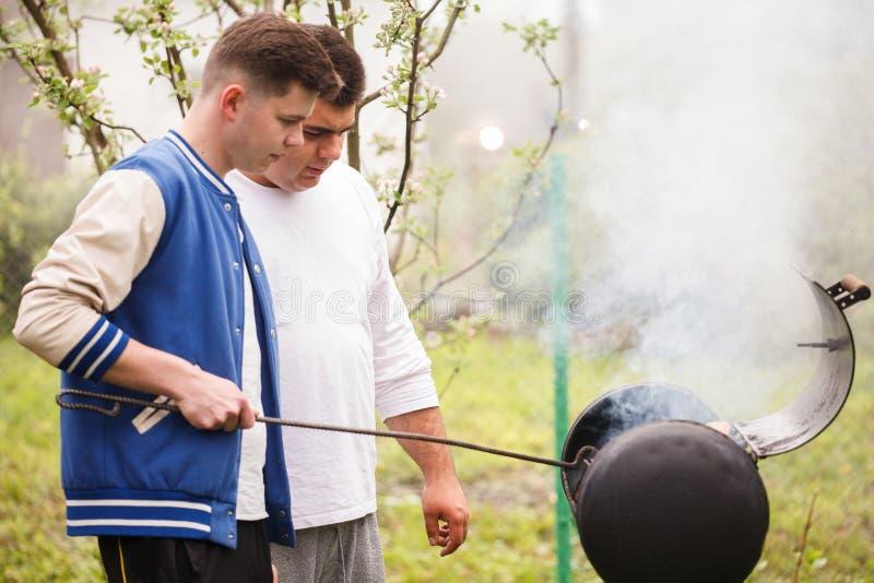 Due giovani che stanno vicino alla griglia del barbecue Accensione del fuoco all'aperto immagine stock libera da diritti