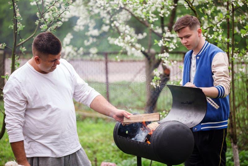Due giovani che stanno vicino alla griglia del barbecue Accensione del fuoco all'aperto immagine stock