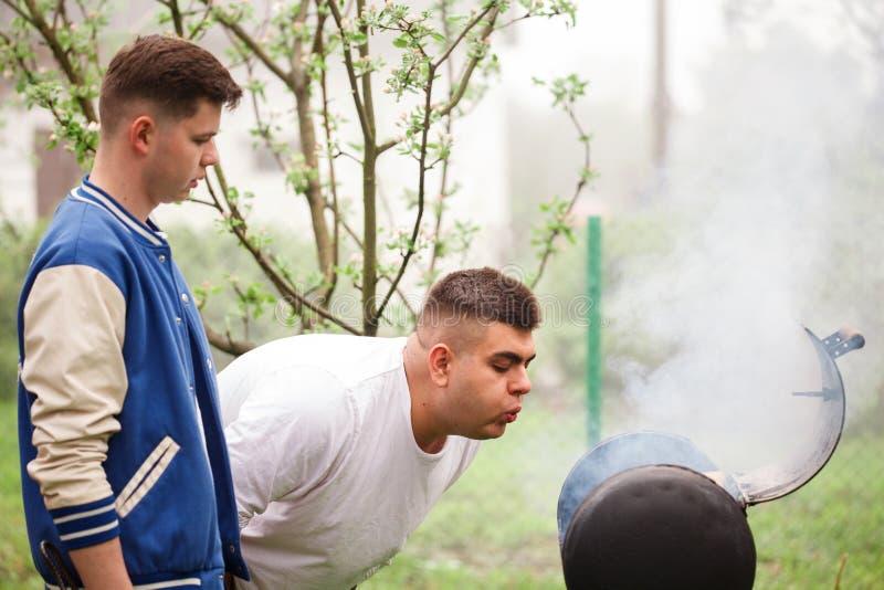 Due giovani che stanno vicino alla griglia del barbecue Accensione del fuoco all'aperto fotografie stock