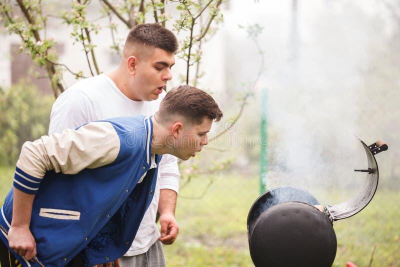 Due giovani che stanno vicino alla griglia del barbecue Accensione del fuoco all'aperto fotografia stock