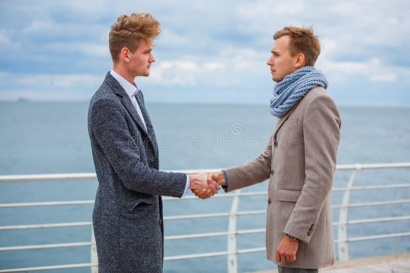 Due giovani che stringono le mani all'aperto vicino al fiume immagini stock