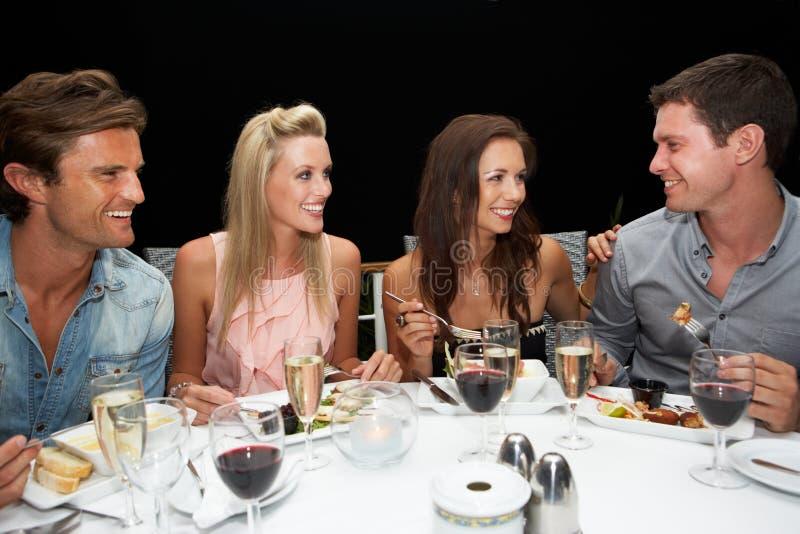 Due giovani coppie in ristorante immagini stock libere da diritti