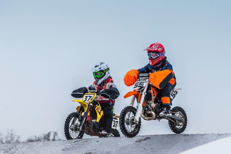 Due giovani corridori del ragazzo sul motociclo guidano attraverso la collina del motocross fotografia stock