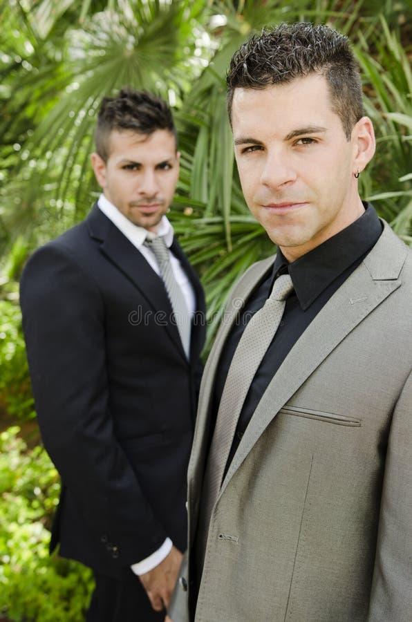 Due giovani del vestito che posano esaminando la vista fotografia stock