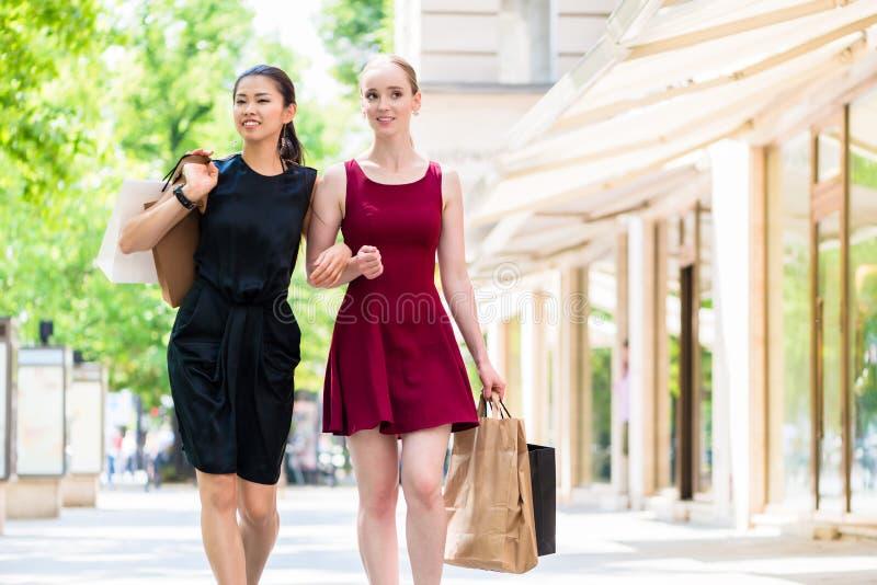 Due giovani donne alla moda che camminano nella città durante l'acquisto fotografia stock