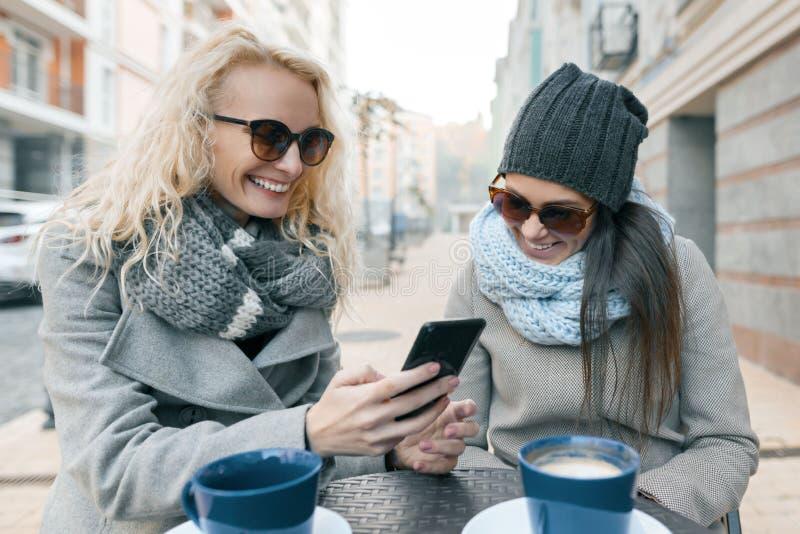 Due giovani donne alla moda sorridenti divertendosi in caffè all'aperto Fondo urbano, donne che ridono esaminando telefono cellul fotografie stock