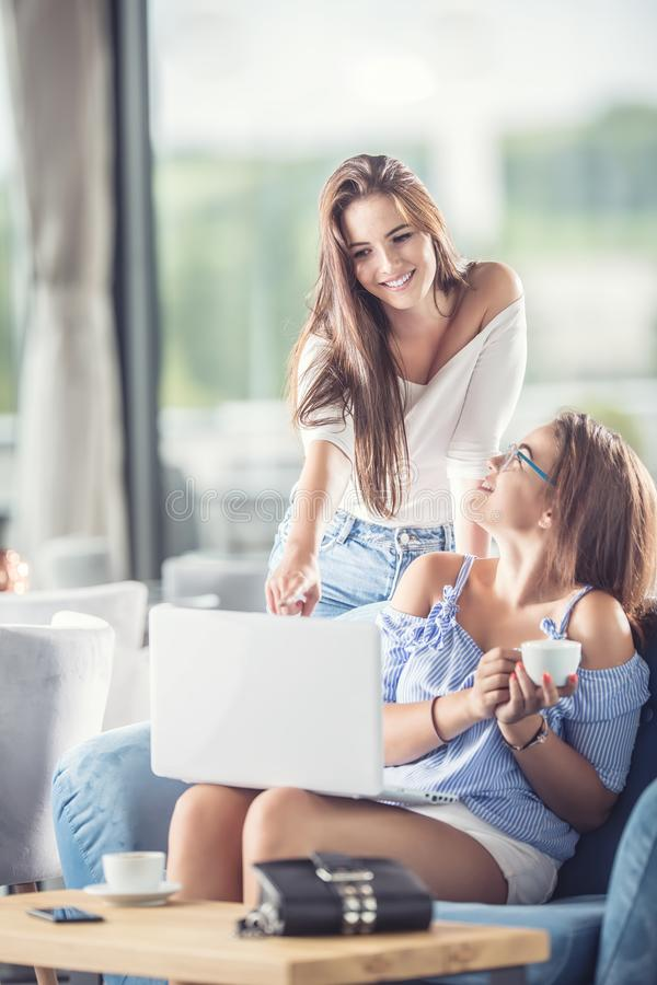 Due giovani donne allegre in una caffetteria con un comforta del computer portatile immagini stock