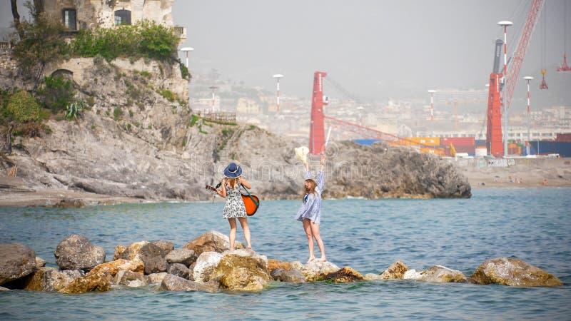 Due giovani donne attraenti ballano appena sulle rocce nella chitarra del gioco e del mare fotografia stock
