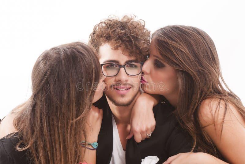 Due giovani donne attraenti che baciano uomo fotografie stock