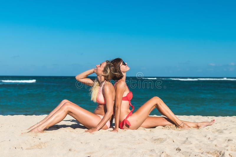 Due giovani donne attraenti che si siedono sulla spiaggia tropicale all'ora legale Isola di Bali fotografie stock