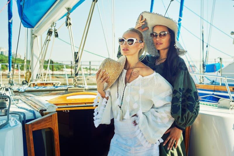 Due giovani donne attraenti stanno riposando su un yacht un giorno soleggiato fotografia stock libera da diritti