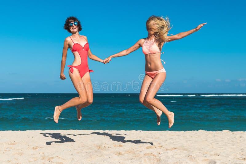 Due giovani donne attraenti stanno saltando sulla spiaggia e stanno divertendo durante la vacanza sull'isola di Bali immagine stock libera da diritti