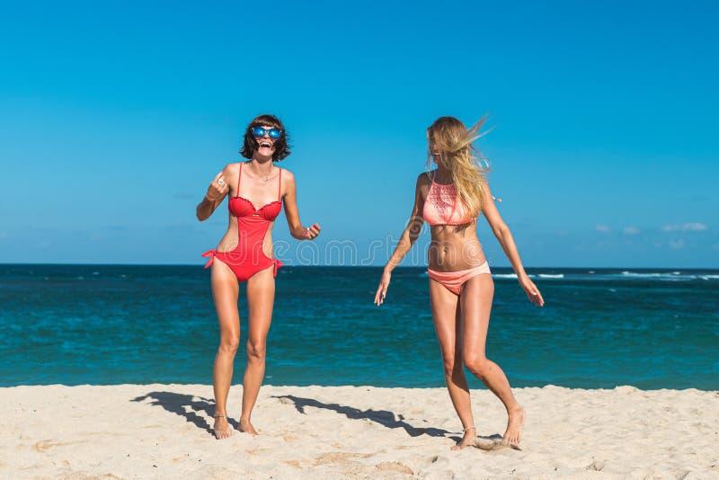 Due giovani donne attraenti stanno saltando sulla spiaggia e stanno divertendo durante la vacanza sull'isola di Bali fotografia stock libera da diritti