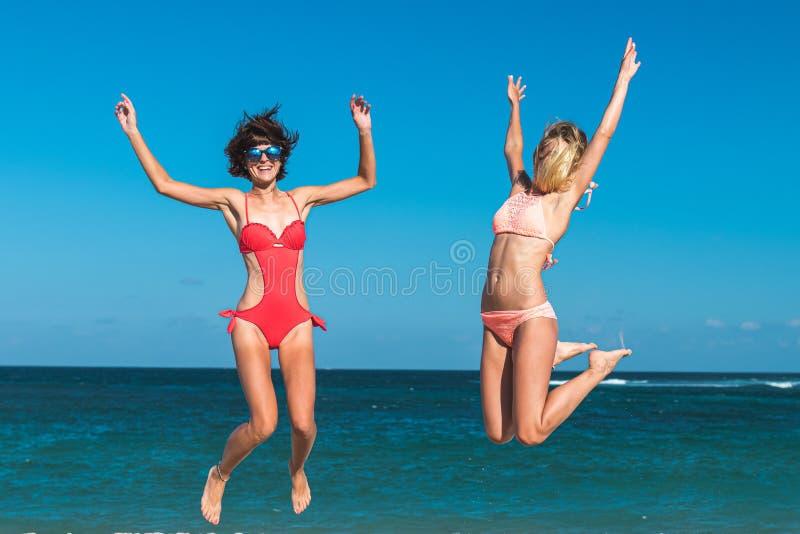 Due giovani donne attraenti stanno saltando sulla spiaggia e stanno divertendo durante la vacanza sull'isola di Bali fotografie stock libere da diritti