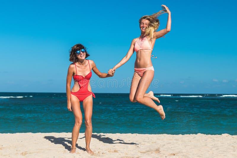 Due giovani donne attraenti stanno saltando sulla spiaggia e stanno divertendo durante la vacanza sull'isola di Bali fotografia stock
