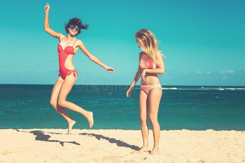 Due giovani donne attraenti stanno saltando sulla spiaggia e stanno divertendo durante la vacanza sull'isola di Bali immagine stock