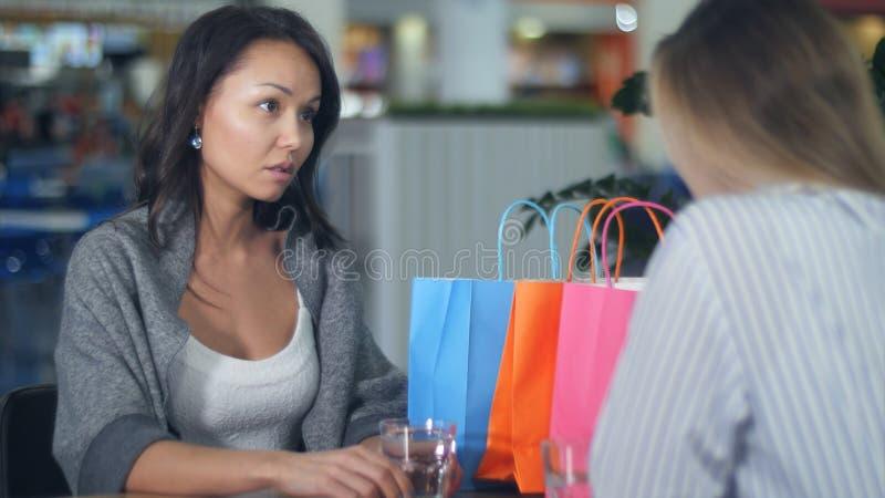 Due giovani donne che hanno discussione del qualcosa che si siede in caffè in centro commerciale immagini stock libere da diritti
