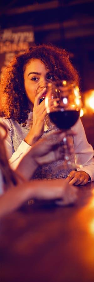 Due giovani donne che mangiano vino rosso in pub fotografie stock