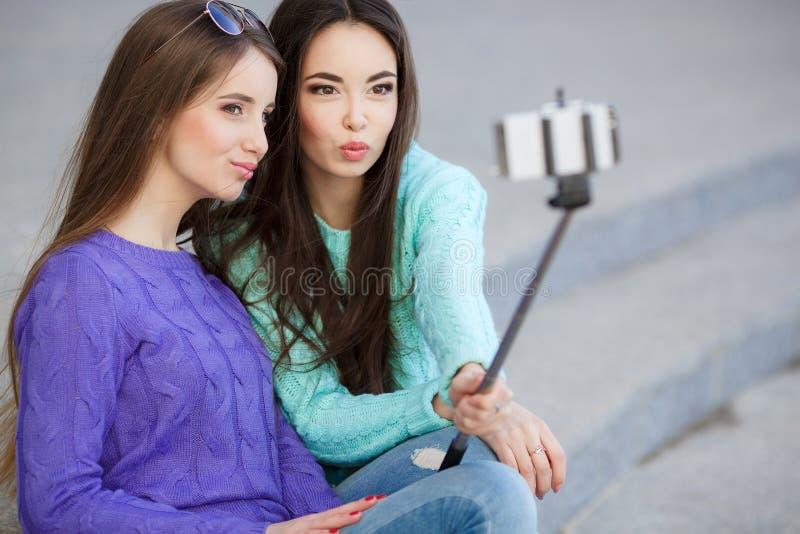 Due giovani donne che prendono le immagini con il vostro smartphone immagini stock