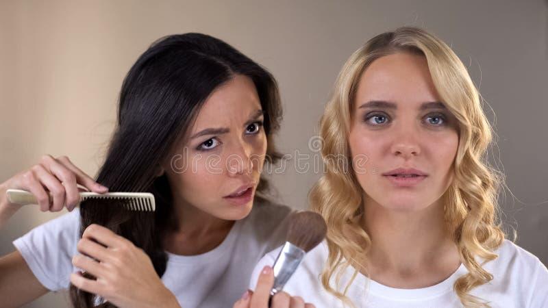 Due giovani donne che preparano per il partito davanti allo specchio, punte di bellezza, attrezzatura fotografia stock libera da diritti