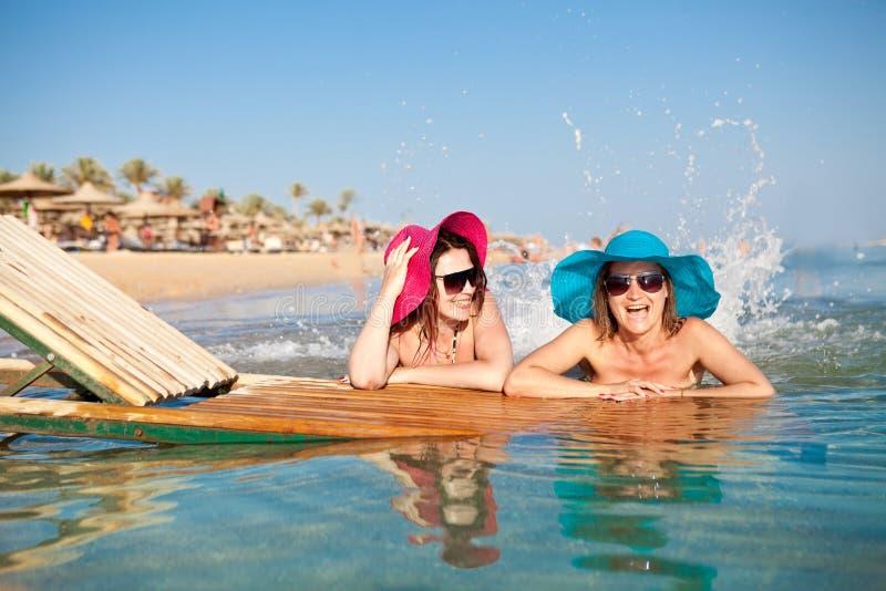 Due giovani donne che schizzano sulla spiaggia fotografie stock libere da diritti