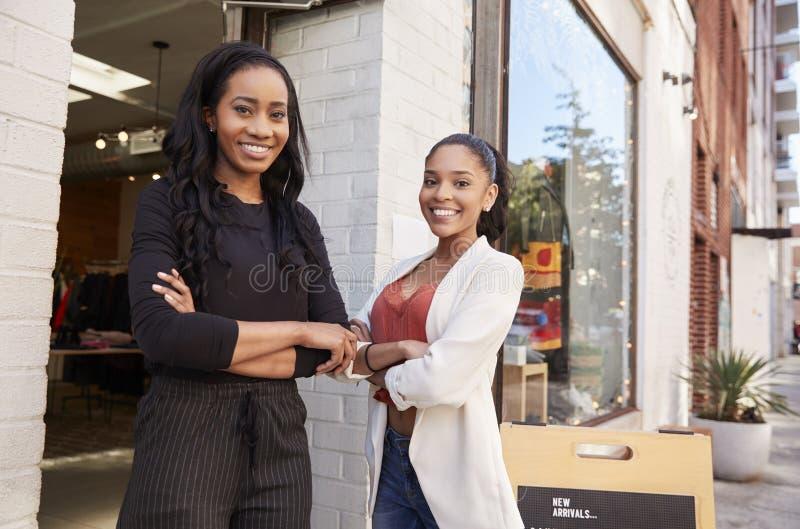 Due giovani donne che sorridono alla macchina fotografica fuori del loro negozio di vestiti fotografia stock libera da diritti