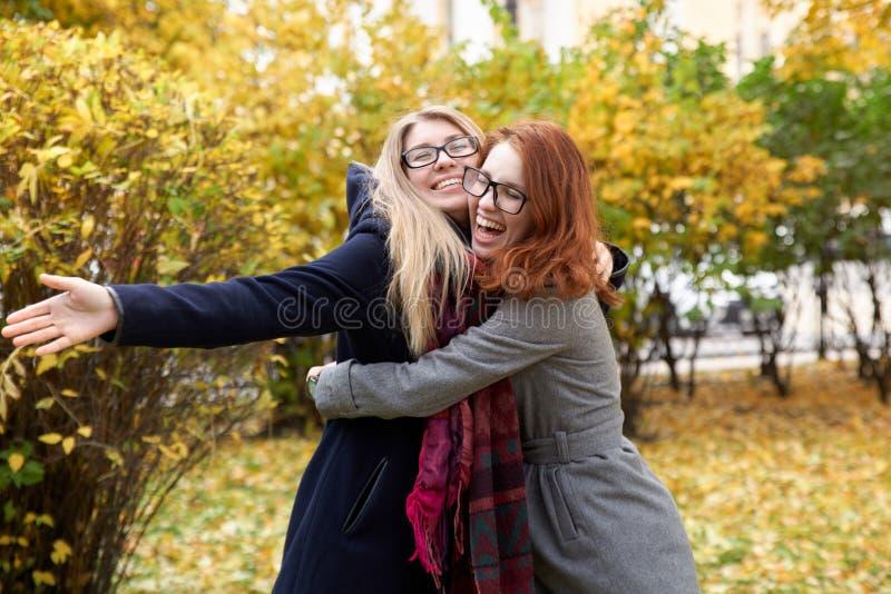 Due giovani donne dell'amico per riunirsi ed abbracciarsi con la a immagini stock