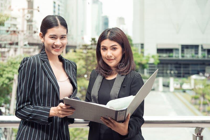 Due giovani donne di affari asiatiche che esaminano la cartella di archivio del documento per analizzare il profitto o la vendita fotografia stock