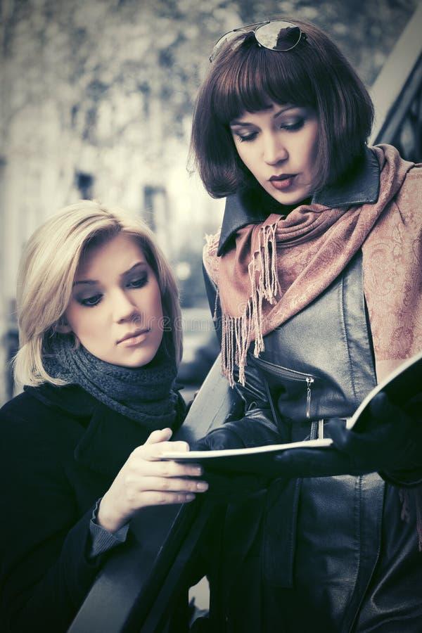 Due giovani donne di affari che leggono la cartella di archivio sulla via della citt? fotografia stock