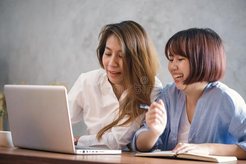 Due giovani donne di affari che si siedono alla tavola in caffè Donne asiatiche che per mezzo del computer portatile e della tazz immagini stock