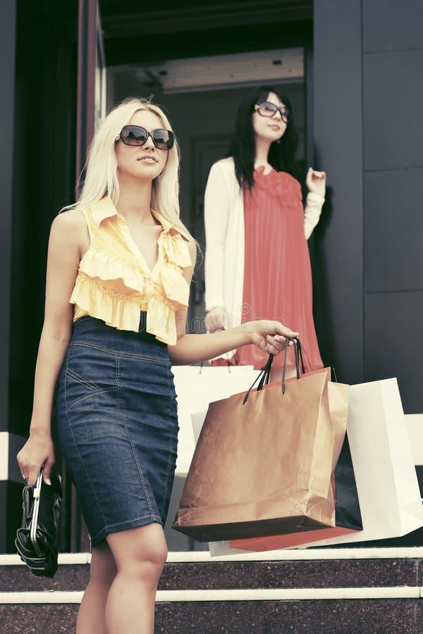 Due giovani donne di modo con i sacchetti della spesa nella entrata del centro commerciale immagine stock