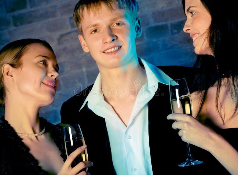 Due giovani donne dolci attraenti ed uomo con i vetri del champagne fotografie stock