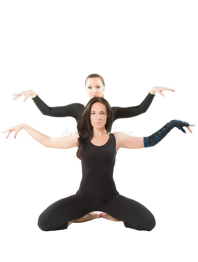 Due giovani donne fanno la stirata sulla posa di yoga immagine stock