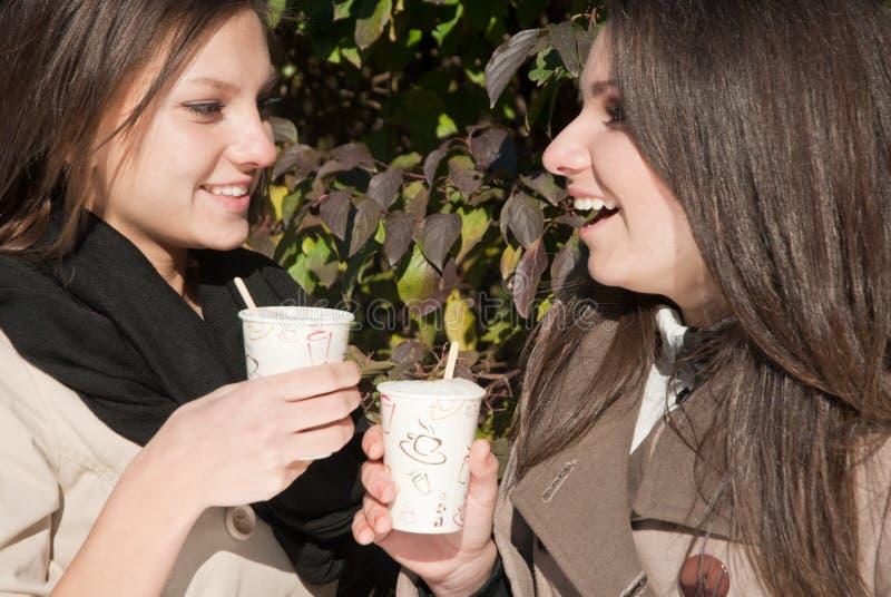 Due giovani donne felici che bevono caffè e tè fotografia stock libera da diritti