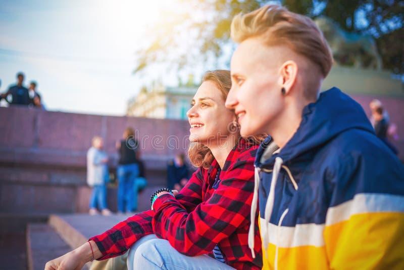 Due giovani giovani donne felici delle ragazze della ragazza comunicano in una città sopra fotografia stock