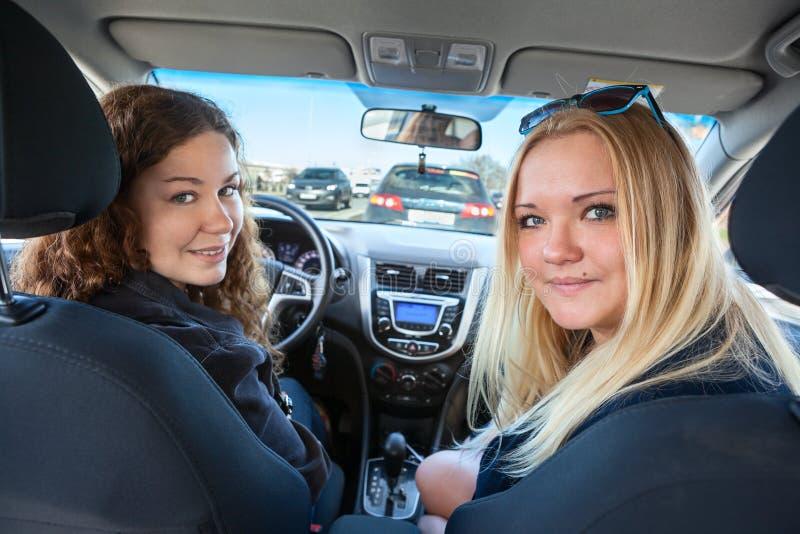 Due giovani donne graziose che si siedono dietro la ruota dell'automobile fotografie stock libere da diritti