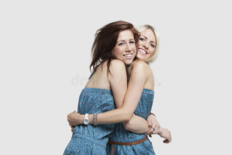 Due giovani donne nei vestiti di salto di corrispondenza che si abbracciano sopra fondo grigio immagini stock