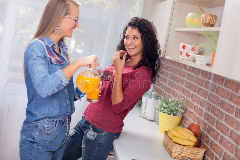 Due giovani donne nella cucina, nella dieta e nel concetto sano di vita fotografie stock