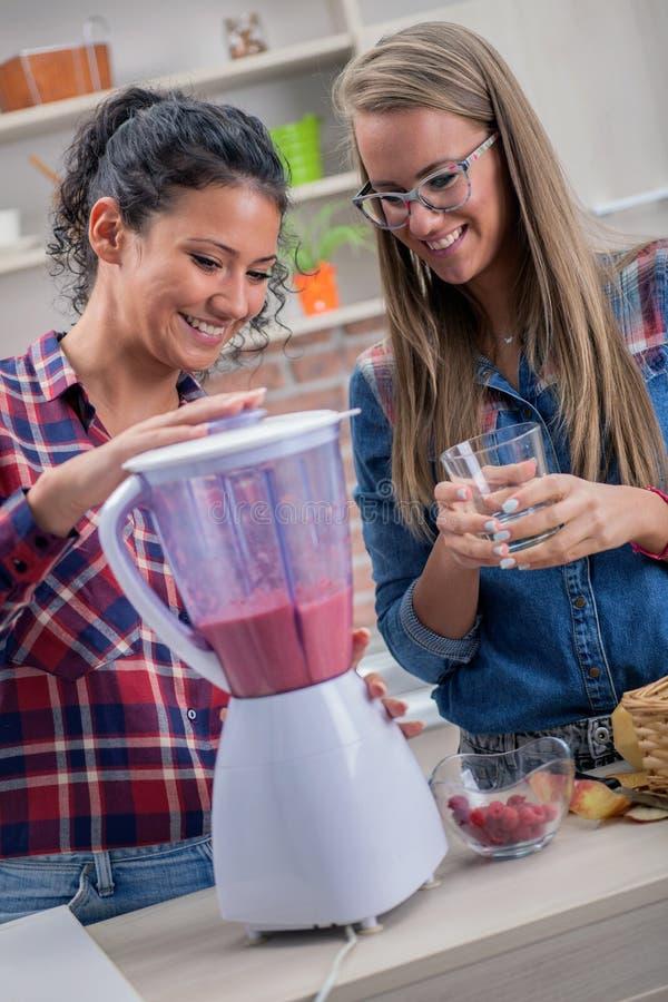 Due giovani donne nella cucina, nella dieta e nel concetto sano di vita fotografia stock libera da diritti