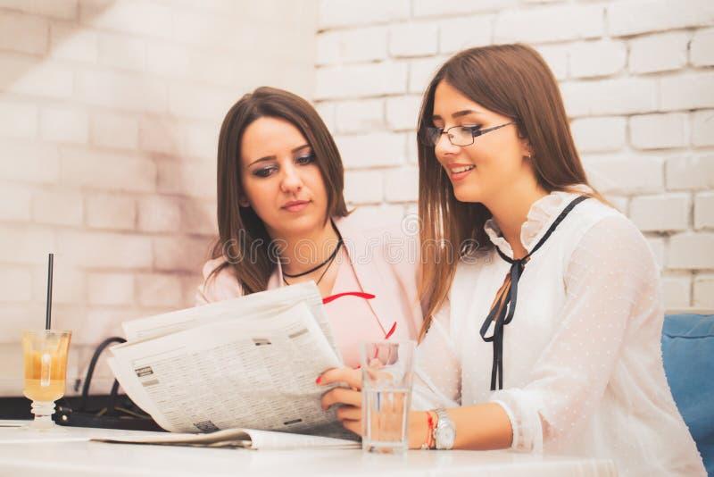 Due giovani donne sorridenti di affari che discutono le notizie fotografie stock libere da diritti