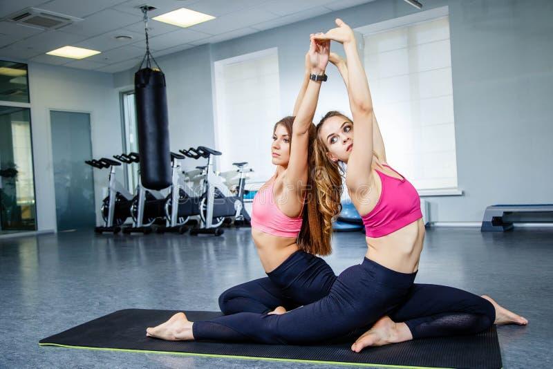 Due giovani donne sportive attraenti che fanno i pilates o esercizio di yoga sulla stuoia nello studio di forma fisica immagine stock libera da diritti