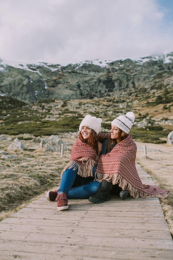 Due giovani donne stanno sedendo sulla montagna con le coperte fotografia stock