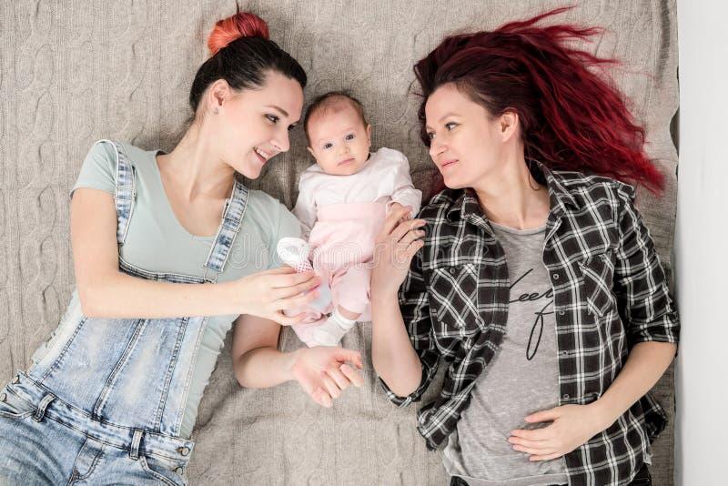 Due giovani donne, una coppia omosessuale lesbica, stanno trovando su una coperta con un bambino Matrimonio omosessuale, adozione immagine stock