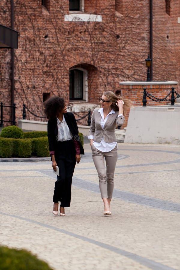 Due giovani e donna di affari attraente che cammina e che ha conversazione Una donna è nera con capelli ricci immagine stock libera da diritti