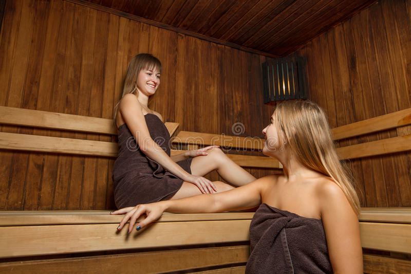 Due giovani e femmine felici nella sauna immagini stock