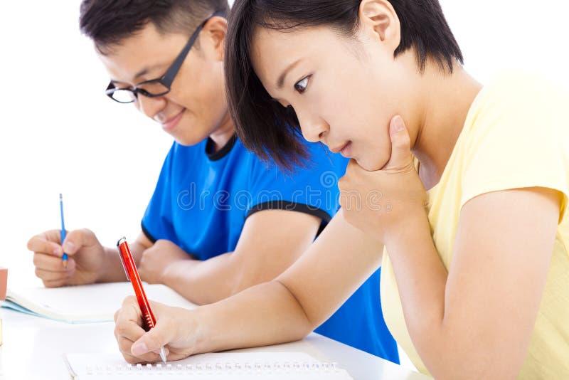 Due giovani esami degli studenti insieme in aula immagine stock
