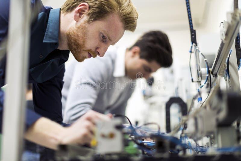Due giovani ingegneri bei che lavorano alle componenti di elettronica fotografia stock libera da diritti