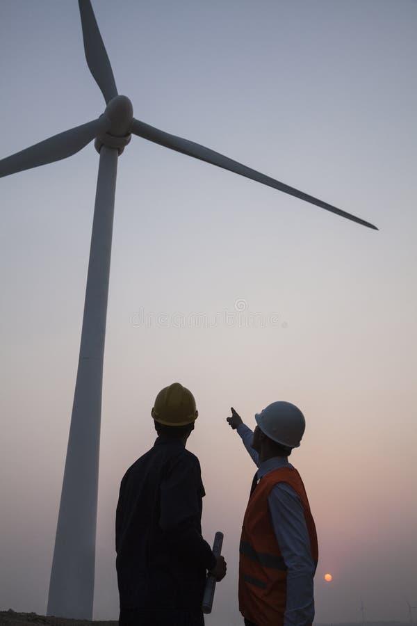 Due giovani ingegneri maschii che stanno accanto ad un generatore eolico al tramonto, indicante su fotografie stock libere da diritti