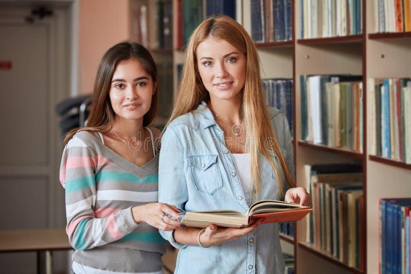 Due giovani libri degli shooses delle studentesse alla biblioteca fotografia stock