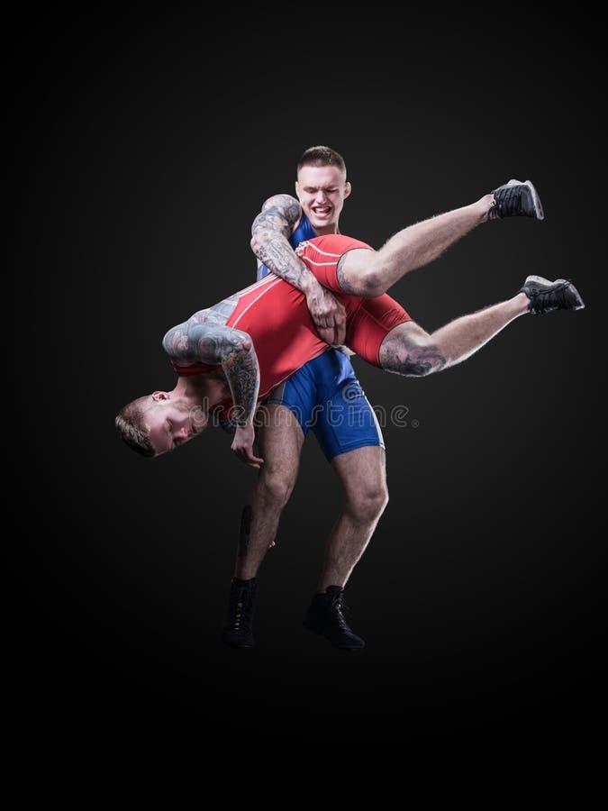 Due giovani lottatori di stile libero isolati su fondo nero fotografia stock